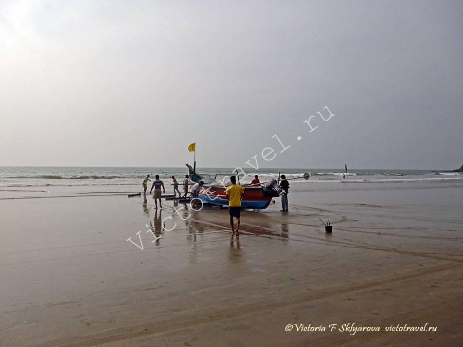 мужчины заносят лодку в море, пляж, Арамболь, Гоа, Индия