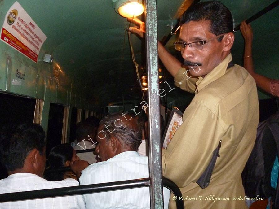 кондуктор в автобусе за работой, Керала, Индия