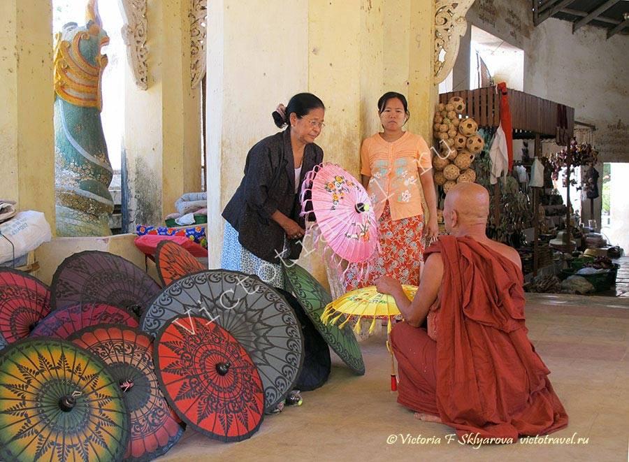 продавцы зонтиков и монах в галерее пагоды, Баган, Мьянма